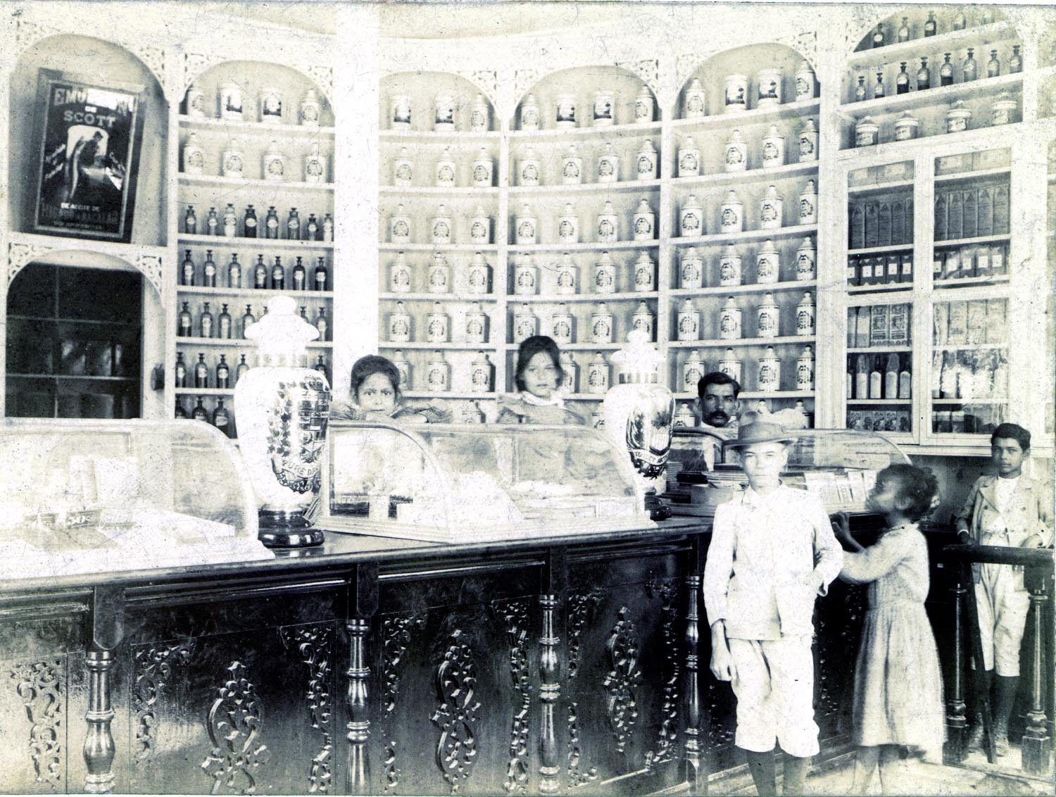 Black and white photograph of the interior of a pharmacy.